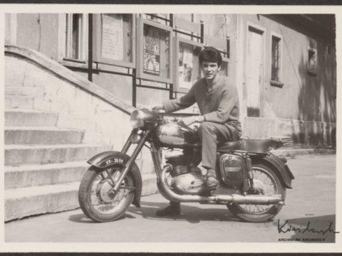 Zdjęcie przedstawiające Krzysztofa Kieślowskiego na motorowerze, pod kinem w Sokołowsku.